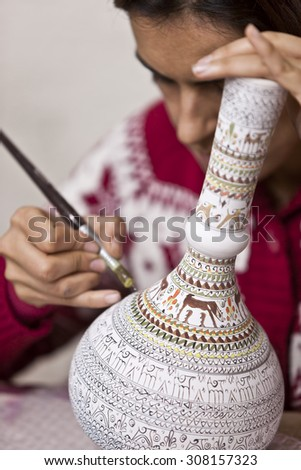 CAPPADOCIA, TURKEY APRIL 17: Mature woman adds detail to a ceramic vase with animal on April 17, 2012 in Cappadocia, Turkey. - stock photo