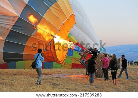 Cappadocia, Turkey - August, 10 2013 :  Ground Crew blasting the burner flame into the balloon envelope to inflate Hot Air Balloon before launching - stock photo