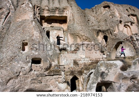 CAPPADOCIA, TURKEY - JAN 4: Mountain home of village people and women walk around the caves on Jan 4, 2012. The first populations of Cappadocia were Hatties, Luvies and Hittites near the 3000 B.C.  - stock photo