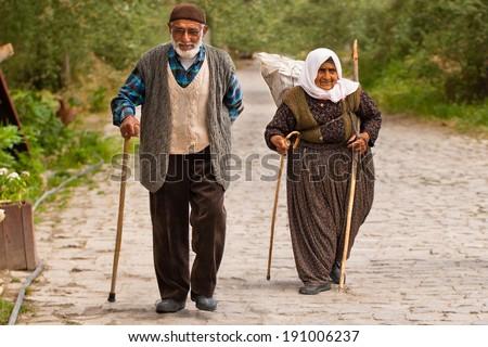 CAPPADOCIA, TURKEY - JUNE 15: Turkish couple walks along stone path on June 15, 2011 in Cappadocia, Turkey - stock photo