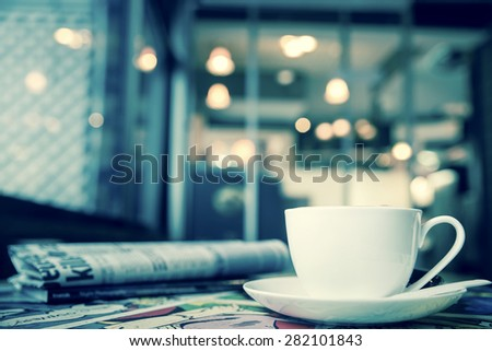 cappuccino and retro alarm clock with blur coffee shop background, vintage green tone - stock photo
