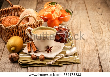 Cappuccino coffee in cup and fruits for breakfast. Tangerines sweet jam on wooden board rustic style - stock photo