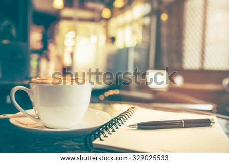 Cappuccino coffee on the table with blur coffee shop background, vintage tone  - stock photo