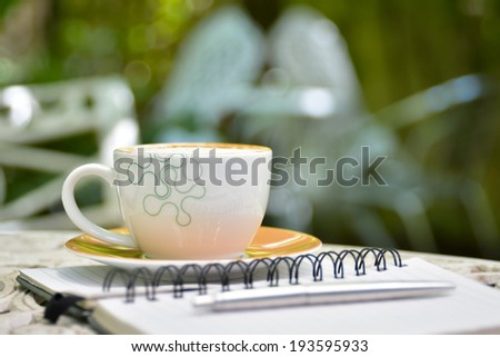 Cappuccino coffee with note book on white table - stock photo