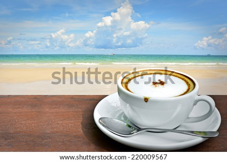 Cappuccino coffee with sea beach background  - stock photo