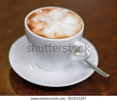 Cappuccino in a white cup on the table - stock photo