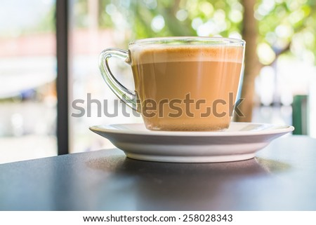 Cappuccino or latte coffee in a clear glass mug. - stock photo