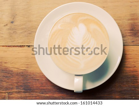 Cappuccino or latte coffee on table with retro filter effect - stock photo
