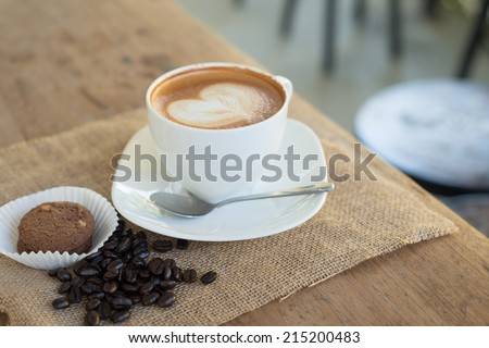 Cappuccino or latte coffee with heart shape in cafe - stock photo