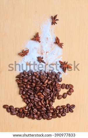 Cappuccino time. Roasted coffee beans placed in shape of cup and with white froth anise decoration on wooden surface background - stock photo
