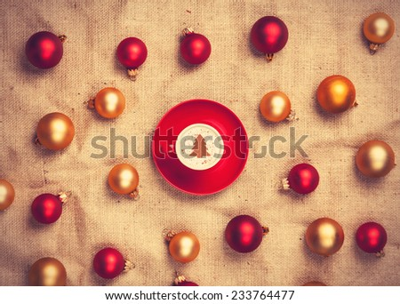 cappuccino with christmas tree shape and with red and gold christmas balls on jute background. - stock photo