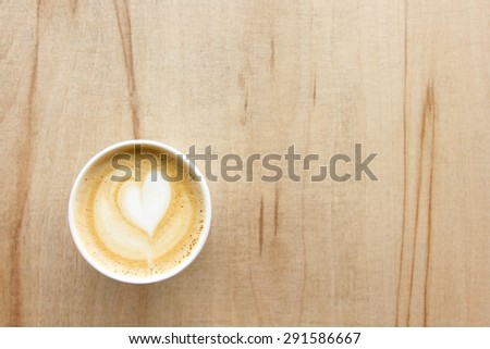 Cappuccino with heart in paper take away cup on light wood table. From above. - stock photo