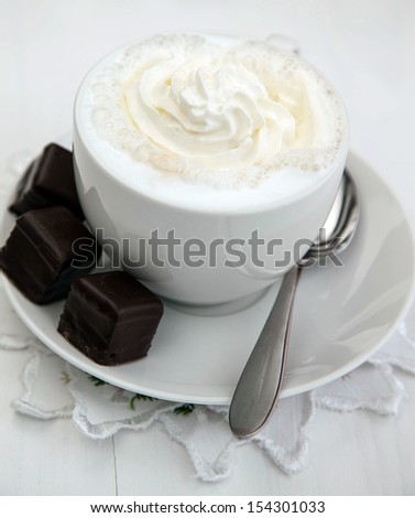 Cappuccino with whipping cream an chocolate covered petite fours - stock photo