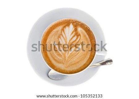 Cappucino with leaf shape foam on white saucer with spoon - stock photo
