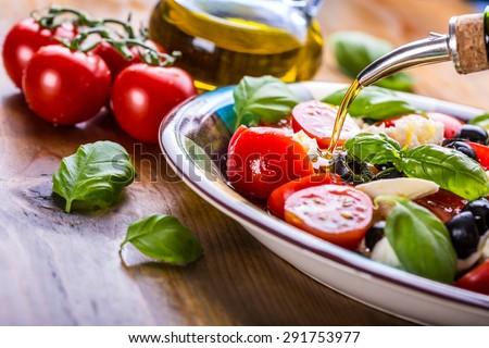 Caprese. Caprese salad. Italian salad. Mediterranean salad. Italian cuisine. Mediterranean cuisine. Tomato mozzarella basil leaves black olives and olive oil on wooden table. Recipe - Ingredients - stock photo