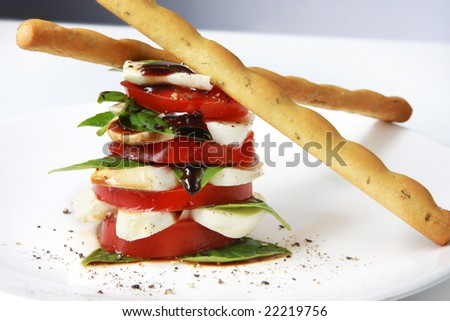 Caprese salad in a stack, with bread sicks.  Tomato and basil salad, with baby mozzarella and balsamic. - stock photo