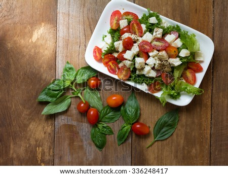 Caprese salad, Italian salad,Tomato mozzarella basil leaves. Top view on wood background - stock photo