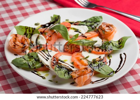 Caprese salad on red and white napkin on the table - stock photo