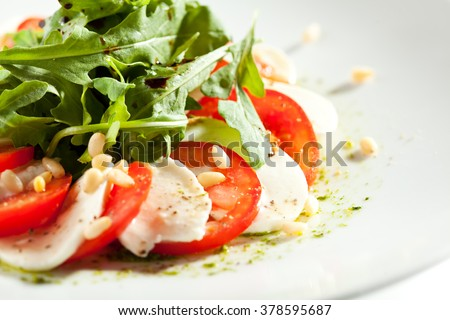 Caprese Salad - Salad with Tomatoes, Mozzarella Cheese and Rocket Salad. Salad Dressing with Pesto Sauce and Pine Nuts - stock photo