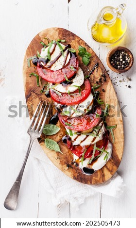 Caprese salad Tomato and mozzarella slices with basil leaves on olive wood cutting board - stock photo