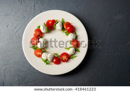 Caprese salad with mozzarella, tomatoes and basil served on white plate. Isolated on gray background. Shot from above. - stock photo