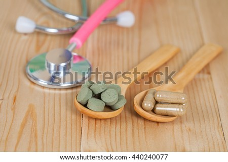 Capsules of herbs on spoon and stethoscope