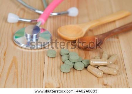 Capsules of herbs on spoon and stethoscope - stock photo