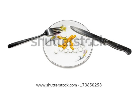 capsules on a saucer with a knife and fork on a white background - stock photo