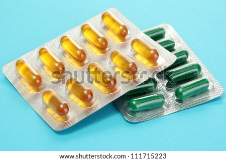 Capsules packed in blisters, on blue background - stock photo