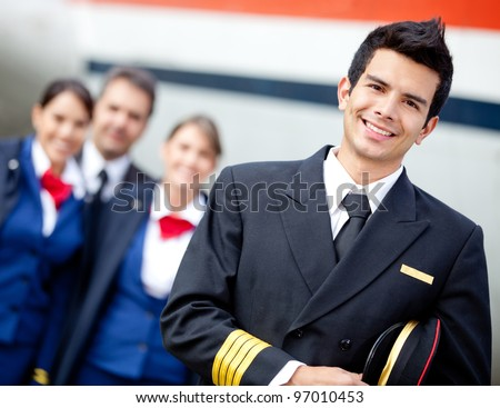 Captain pilot with cabin crew and an airplane at the background - stock photo
