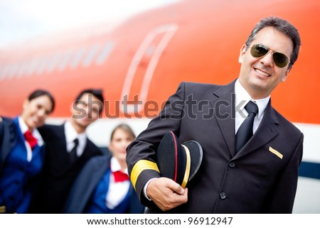 Captain pilot with his cabin crew at the airport - stock photo