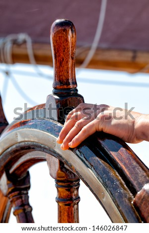 Captain's hand on the wheel of the ship. Concept for leadership, guidance, responsibility, smooth sailing - stock photo