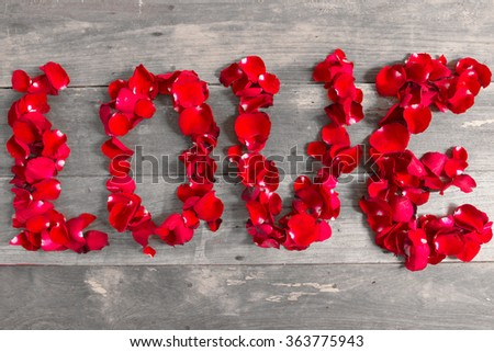 Caption word love on old wood background. Love inscription from the petals of roses. - stock photo