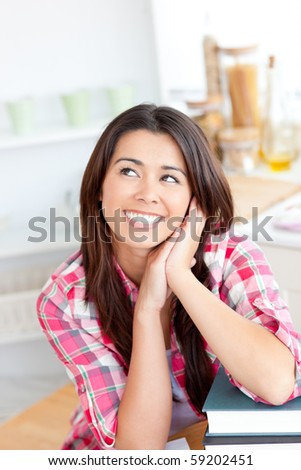 Captivating asian woman sitting in the kitchen with her books at home - stock photo