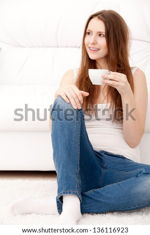 Captivating woman holding a cup sitting on the floor at home - stock photo
