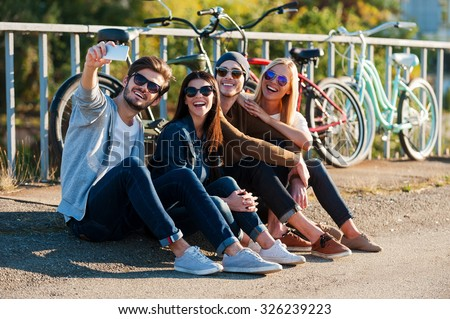 Capturing fun. Group of young smiling people bonding to each other and making selfie by smart phone while sitting outdoors together with bicycles in the background  - stock photo