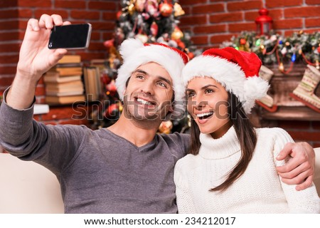 Capturing happy moments. Beautiful young loving couple bonding to each other and smiling while making selfie with Christmas Tree in the background  - stock photo