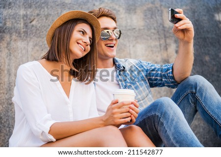 Capturing the bright moments. Happy young loving couple making selfie with smart phone while leaning at the wall - stock photo