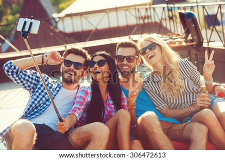 Capturing the moment. Top view of four cheerful young people bonding to each other and making selfie on smart phone while sitting on the roof - stock photo