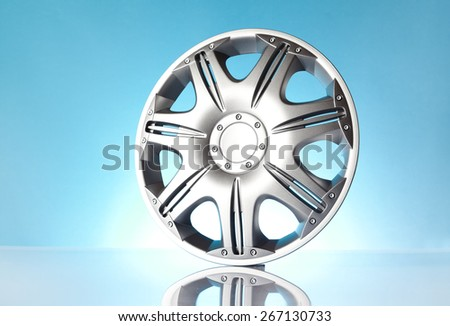 Car accessories - isolated car hubcap on blue background - stock photo