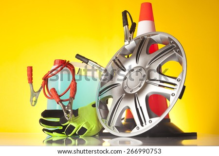 Car accessories - washer fluid with jump start cables and pair of green gloves with traffic cone and an alloy wheel on yellow background - stock photo