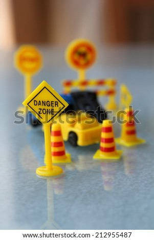 car Accident zone cordoned off with a yellow stop sign post. two cars with a major collision with one car toppled by another brown car & area cordoned by yellow barricades - stock photo