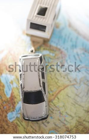 Car and caravan on globe. Miniature concept - stock photo