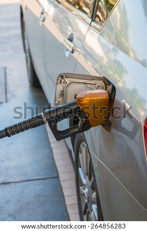 Car at gas station being fill fuel - stock photo