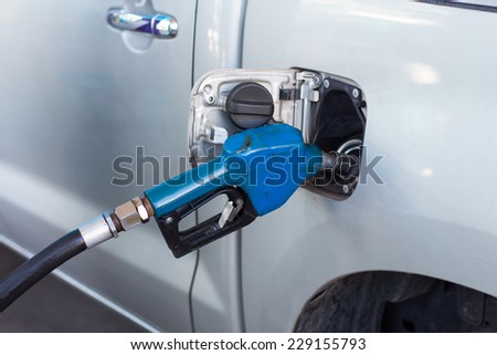 Car at gas station being filled with fuel - stock photo