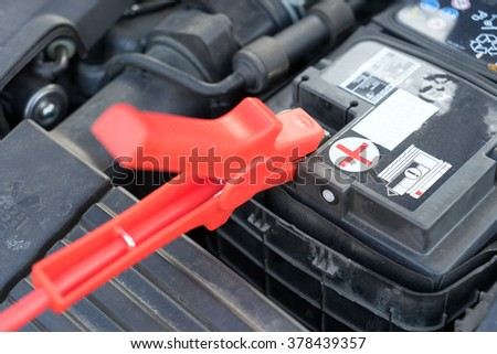 Car battery and starter booster cable / Car battery - stock photo
