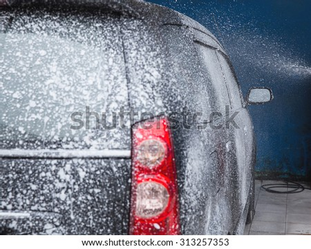 car being washed in car wash station, taken from behind the car - stock photo