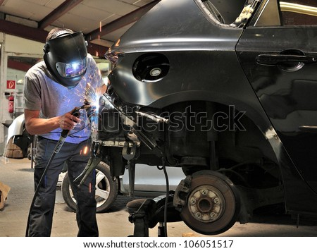 Car body worker welding car body. - stock photo