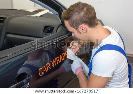 Car branding specialist puts logo with car wrapping foil or film on vehicle door - stock photo
