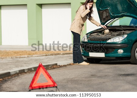 Car breakdown couple calling for road assistance look engine - stock photo